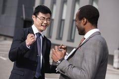 Jongelui die multi-etnische zakenlieden in formalwear het vieren succes glimlachen royalty-vrije stock foto's