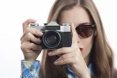 Jongelui die positieve vrouwenfotograaf met camera charmeren stock foto's