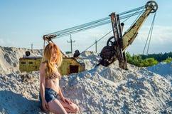 Jongelui die sexy meisje met lang mooi haar in denimborrels en een zitting van het bikinibadpak op een berg van zand in betoveren Royalty-vrije Stock Foto's