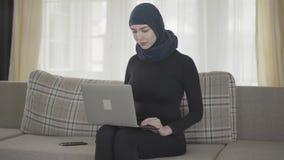 Jongelui die succesvol zeker meisje in achterkleren en mooi hoofddeksel glimlachen die met haar laptop zitting aan werken stock footage