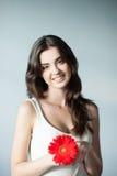 Jongelui die toevallig meisje met rode bloem glimlachen Stock Afbeelding