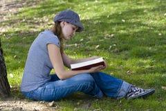 Jongelui die van een boek genieten Stock Afbeelding