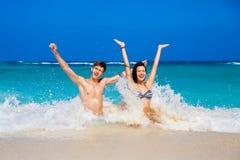 Jongelui die van gelukkig paar op tropisch strand houden Stock Foto's