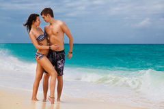 Jongelui die van gelukkig paar op tropisch strand houden Royalty-vrije Stock Foto's
