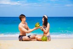 Jongelui die van gelukkig paar op tropisch strand, met kokosnoten houden Stock Foto