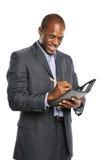 Jongelui die zwarte zakenman glimlachen die nota's neemt royalty-vrije stock fotografie