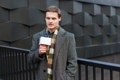 Jongelui kleedde stylishly mannelijke TV-verslaggever rapporteert over de straat in de stad stock foto