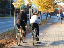 Jongelui koppelt, een kerel en een meisje, berijdt een fiets langs de weg door de herfstgulitsa in de dag Ontspan het actieve lev stock afbeelding