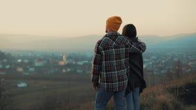 Jongelui koppelt in liefde van reizigers die zich op de horizon en de bergen verheugen Achter mening stock videobeelden