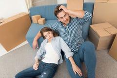 Jongelui koppelt tijdens een beweging aan een nieuwe flat Bewegende jonggehuwden aan nieuwe huisvesting stock afbeelding