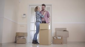Jongelui koppelt zich het bewegen in een nieuw huis Een paar bevindt zich op de drempel naast de dozen en het koesteren Familie stock videobeelden