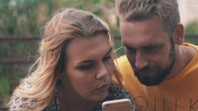 Jongelui in liefdepaar die smartphone op bank gebruiken De zomer winderige dag Het lopen stock video