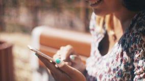 Jongelui in liefdepaar die smartphonezitting op bank gebruiken De zomer winderige dag gelukkig stock footage