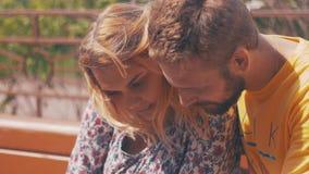 Jongelui in paar die smartphone op bank gebruiken De zomer winderige dag Liefde geluk stock videobeelden