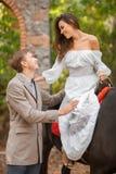 Jongelui valt in liefdepaar op een datum openlucht Vrouw en man die met paard in de herfstpark lopen Stock Afbeelding