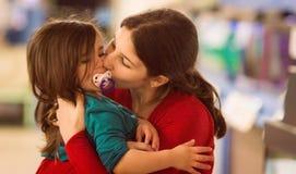 Jongelui van een jong meisje die haar zuster kussen Stock Foto