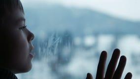 Jongen achter venster in de winter stock videobeelden