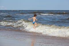 Jongen achtervolgen golven stock foto's