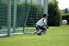 Jongen als bewaarder bij een voetbalspel stock afbeeldingen