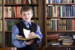 Jongen in bibliotheek Stock Foto's