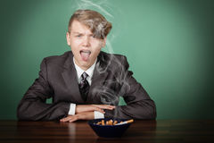 Jongen bij bureau met asbakje van sigaretten Stock Afbeeldingen