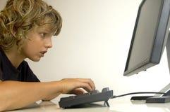 Jongen bij computer stock foto's