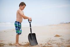Jongen bij het strand met een schop Stock Foto