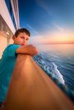 Jongen bij het traliewerk van een cruiseschip bij zonsondergang stock foto's