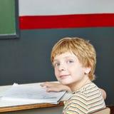 Jongen bij lijst in school Stock Foto's