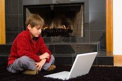 Jongen bij Open haard op Computer. Royalty-vrije Stock Afbeeldingen