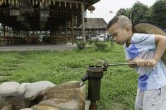 Jongen bij waterpomp stock foto