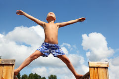 Jongen in borrels die zich op raad tegen wolken bevinden Royalty-vrije Stock Foto