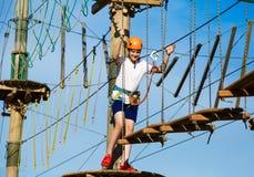 Jongen in bosavonturenpark Het jonge geitje in oranje helm en witte t-shirt beklimt op hoge kabelsleep Openlucht beklimmen stock fotografie