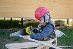 jongen in bouwvakker met een handsaw die een houten Raad zaagt stock afbeeldingen