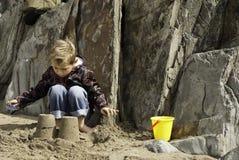 Jongen de bouwzandkasteel op Rocky Beach Royalty-vrije Stock Afbeelding