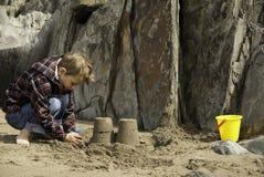 Jongen de bouwzandkasteel op Rocky Beach Royalty-vrije Stock Afbeeldingen