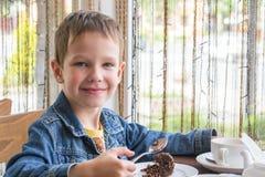 Jongen in de koffie die een heerlijke cake eten Royalty-vrije Stock Foto's