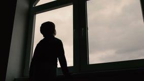 Jongen de status bij venster en bekijkt de hemel stock footage