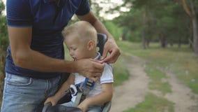 Jongen in de zetel van de kindfiets, vaderslijtage een veiligheidsgordel stock videobeelden