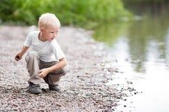 Jongen dichtbij de rivier Stock Afbeeldingen