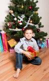 Jongen dichtbij een nieuw-jaarboom Stock Afbeeldingen