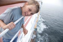 Jongen dichtbij leuningen op dek van schip royalty-vrije stock afbeeldingen