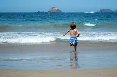 Jongen die aan het overzees loopt Stock Afbeeldingen