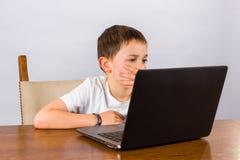 Jongen die aan laptop werkt royalty-vrije stock foto's