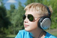 Jongen die aan muziek door hoofdtelefoons luisteren Stock Foto's