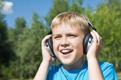 Jongen die aan muziek luistert Stock Afbeeldingen
