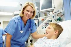 Jongen die aan Vrouwelijke Verpleegster In Emergency Room spreken Stock Foto