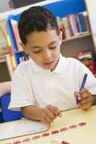 Jongen die aantallen in primaire klasse leert te schrijven Stock Afbeelding