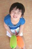 Jongen die & ballons glimlacht houdt Royalty-vrije Stock Foto's