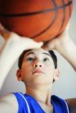 Jongen die basketbal schieten stock afbeeldingen